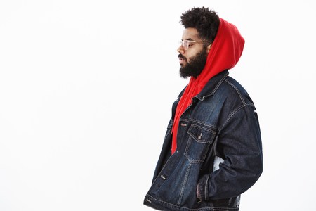 Profile shot of dreamy and thoughtful handsome stylish african american guy in denim jacket over red hoodie, looking down holding hands in pockets as walking and thinking, making important decision