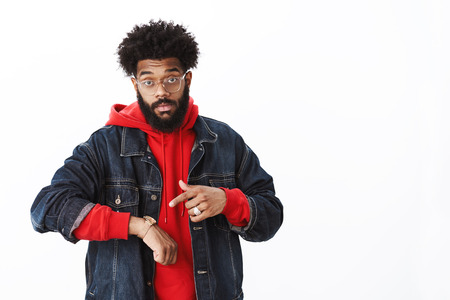 Intense masculine african american bearded man with afro hairstyle in glasses pointing at watch as hinting to move faster, being late to meeting over gray wall Stock Photo