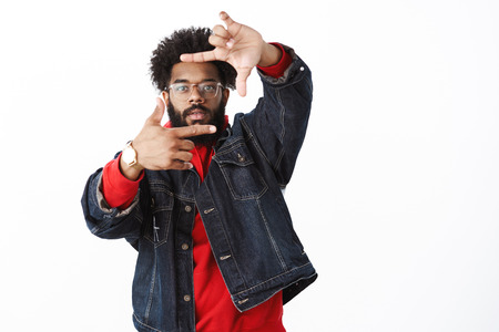 Studio shot of cool and stylish african american male producer in glasses stepping back as pulling hands towards camera with frames gesture looking through. Stock Photo