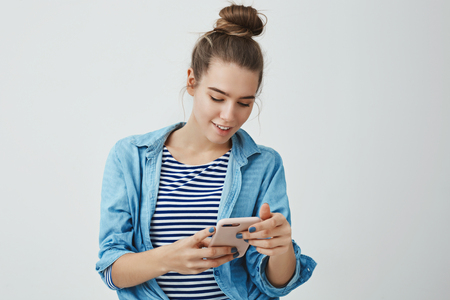 Intrigued amused good-looking fashionable woman 25s reading interesting invitation message holding smartphone looking display excited smiling broadly, edditing selfie using filter app liking result