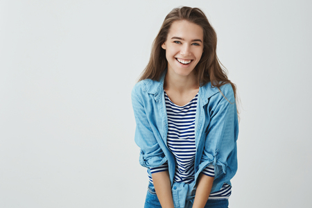 Smiling attractive happy young girl laughing carefree having fun grinning joyfully bending forward cute silly, posing silly. Tender european woman chuckling flirty looking, standing white background