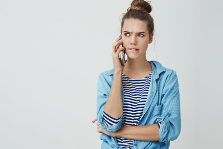 Girl facing tough troublesome choice perplexed biting lower lip frowning looking seriously aside holding smartphone talking having hard conversation, thinking, taking decision, white background