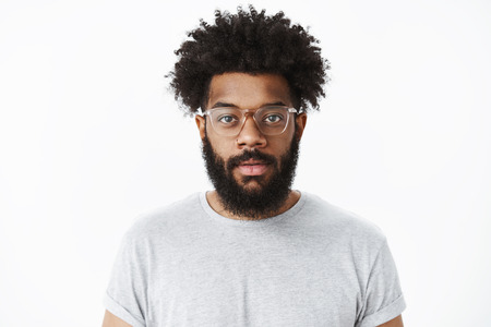 Close-up shot of attractive friendly-looking african american bearded man in glasses with pierced nose and afro hairstyle smiling joyfully at camera feeling positive, standing against gray background