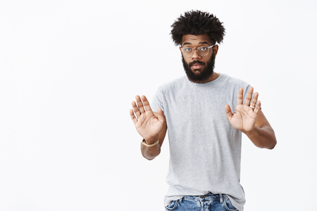 Slow down and explain. Portrait of calm confident handsome african american masculine bearded guy with curly hair raising palms in stop, trying prevent friend from bad decisions over gray background
