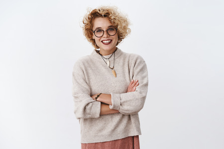 Portrait of bright and enthusiastic hipster girl wearing makeup and glasses holding hands crossed over chest as feeling chilly, looking happily at finished artwork being upbeat over white background