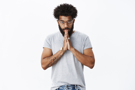 Student bowing to sensei. Portrait of devoted and serious-looking calm african american adult bearded guy in glasses with tattoos and piercing nodding making namaste greeting with hands together Stock Photo