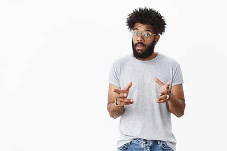 Handsome masculine bearded african american man in glasses with tattoos gesturing and waving hands as talking, explaining how product work raising eyebrows, describing thing to customer