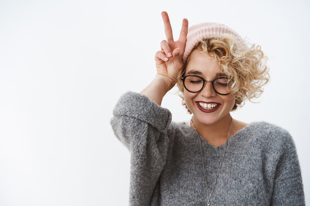 Close-up shot of woman loving winter and holidays having fun feeling happy and tender close eyes joyful wearing beanie and sweater smiling broadly showing peace, victory sign near head