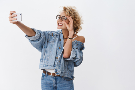Creating memory on spot. Portrait of charming enthusiastic and stylish good-looking blond woman in denim jacket and glasses smiling broadly at smartphone while taking selfie on front camera Stock Photo