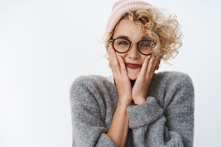 Portrait of excited and cute enthusiastic good-looking girlfriend feeling upbeat and thrilled before holiday trip smiling holding palms on cheeks wearing pink beanie and sweater over white wall Stock Photo