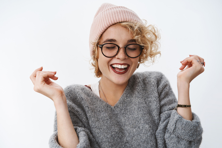 Carefree emotive and enthusiastic good-looking girlfriend in pink beanie and sweater close eyes raise hands and smile broadly wearing glasses having fun and feeling awesome playing in snow