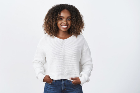 Girl having fun talking to interesting person. Portrait of joyful charismatic smiling african-american young woman with curly hair in sweater holding hands in pockets and smiling broadly at camera