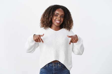 Studio shot of stylish african-american joyful female coworker in sweater pointing down and showing awesome promotion recommending look and check out advertisement, smiling happily over white wall