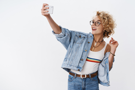 Looking awesome, shall online. Stylish confident and charismatic european young woman with short curly haircut in glasses and denim taking selfie on smartphone extending hand with mobile phone