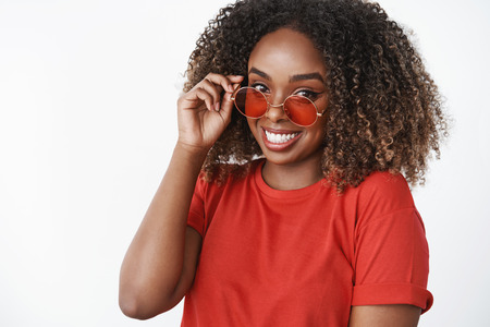 How you doing sunny. Portrait of cute african-american modern woman in red t-shirt and trendy sunglasses touching rim carefree and gazing delighted tender at camera having good mood over white wall Imagens