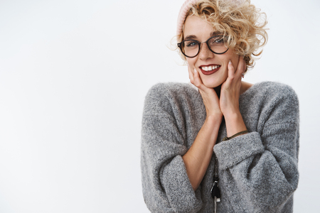 Getting all comfy in winter. Portrait of charming and tender european woman in cozy sweater and glasses touching her face gently feeling sensual and gentle posing delighted over white wall