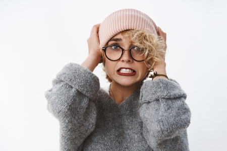 Geez it freezing cold. Portrait of shocked displeased and panicking cute blond girl pulling beanie on head clenching teeth anxiously and afraid popping eyes troubled over white background
