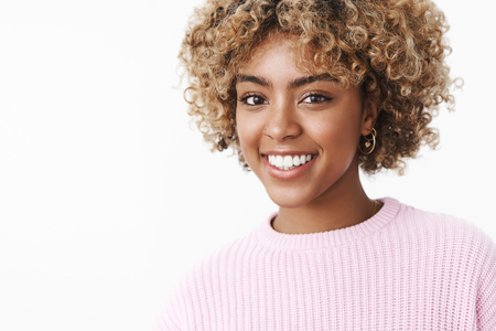 Good-looking happy african american female student with afro blond haircut in sweater with joyful broad smile gazing satisfied at camera with carefree expression having fun, laughing happily Foto de archivo