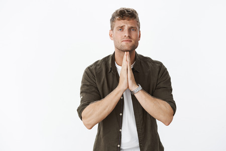 Please really need it. Portrait of handsome blond man begging holding hands in pray frowning in sorrow, looking hopeful at camera as supplicating asking apology sincere over gray background