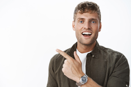 Hey check out this you gonna like it. Portrait of handsome charismatic blond guy with blue eyes and white broad smile pointing at upper left corner curiously smiling delighted against gray background