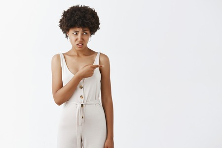 Indoor shot of displeased intense good-looking dark-skinned girl with white overalls frowning and stooping pointing and looking right with confused and doubtful expression, being unsure and questioned