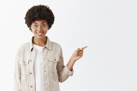 Girl suggesting grab some coffee and continue conversation in lovely cafe. Portrait of charming african american in glasses and shirt with afro hairstyle, pointing right with index finger and smiling