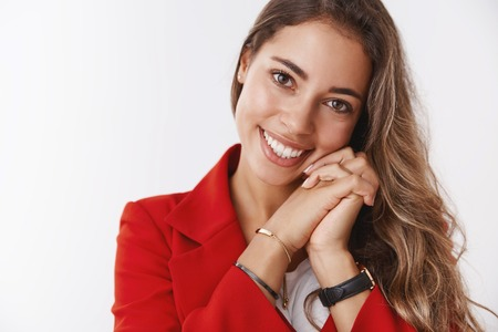 Charming romantic curly-haired modern woman wearing red jacket leaning head pressed hands smiling tenderly fullfilled, happy grinning gazing camera delighted expressing wellbeing positive vibes
