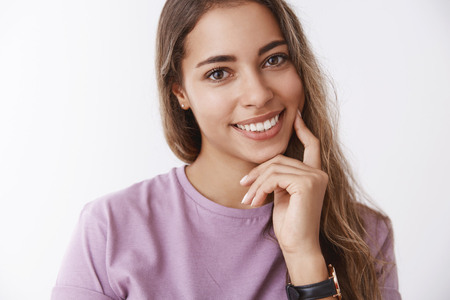 Close-up hispanic cute tender woman 25s tilting head flirty smiling giggling joyfully, feeling happy, touching cheek finger, taking care skin, fighting facial scars, delight skincare products result