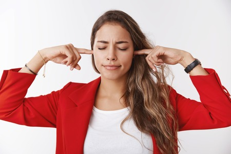 Unwilling hear. Girl shuts ears close eyes pursing lips displeased irritated cannot concentrate hearing interrupting bothering noise standing annoyed plugging earholes using index fingers