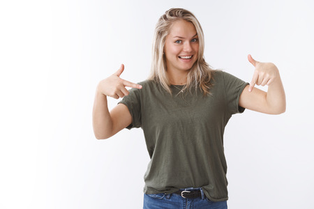 Excited and carefree attractive european blonde asking see down indicating bottom copy space with index finger and smiling mysteriously and cheeky over white background Stock fotó