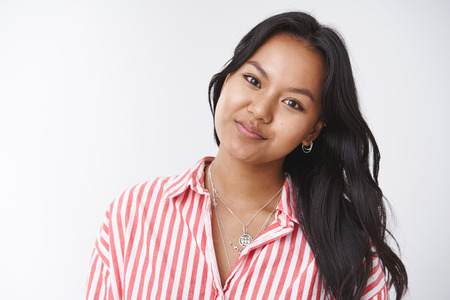 Authentic shot of young attractive female asian student tilting head and smiling tender at camera sending warm gaze as having good mood and gentle attitude, posing over white background