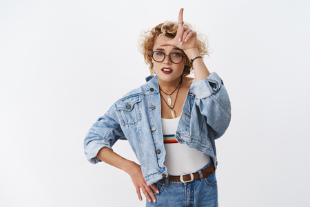Girl looking with dismay at losers. Portrait of arrogant and confident good-looking stylish woman with short blond haircut mocking rival showing L letter on forehead and grimacing like snob
