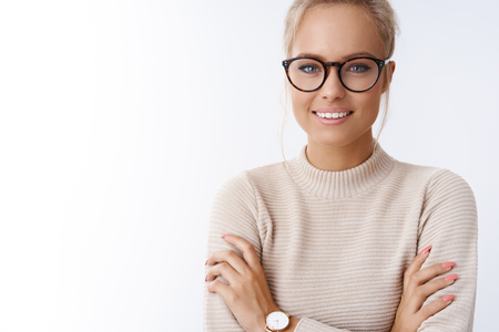 Close-up shot of stylish glamour charming caucasian blond woman in glasses wearing watch warm sweater cross arms against chest, smiling pleased with positive attitude aiming success over white wall Imagens