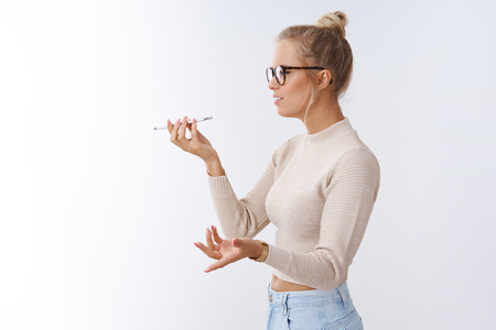 Woman arguing on phone talking via speaker holding smartphone near mouth spread hands in dismay bothered and intense having serious argument sending voice message over white background