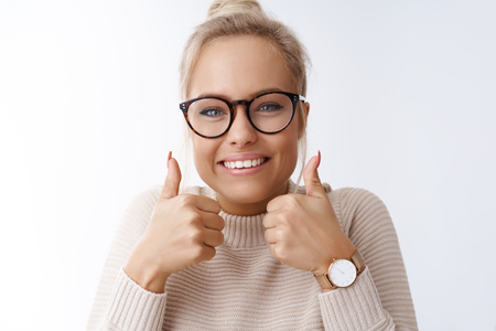 You can do it, believe. Portrait of optimistic friendly-looking excited cheerful young blond woman in glasses showing thumbs-up in support and approval, giving positive opinion over white background