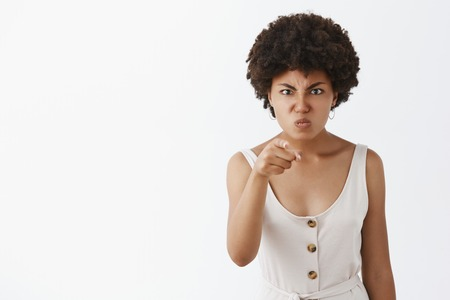 Displeased angry and disappointed dark-skinned wife with afro hairstyle, pointing with index finger at camera, frowning, pulling face from anger, being outraged on someone