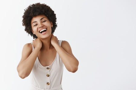 Joyful and happy girl feeling great spending time with close friends. Portrait of beautiful carefree emotive dark-skinned female coworker in trendy outfit, holding hands on neck and laughing out loud