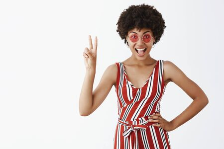 Portrait of joyful self-assured emotive and stylish african american woman in trendy sunglasses and striped showing victory sign with raised hand and smiling