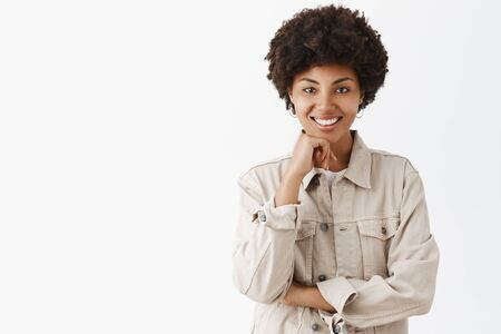 Studio shot of stylish good-looking dark-skinned female in beige shirt with afro hairstyle holding hand on chin and smiling broadly