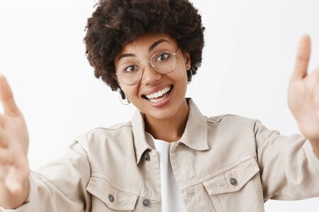 Close-up shot of friendly and cute african american female in transparent glasses and shirt pulling hands towards camera to take selfie