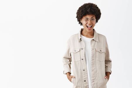 Good-looking confident dark-skinned tomboy in glasses and beige shirt, winking, holding hands in pockets and smiling with daring expression over gray background