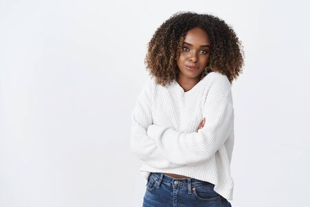 Cute tender african-american girlfriend in sweater hugging herself with hands crossed over body