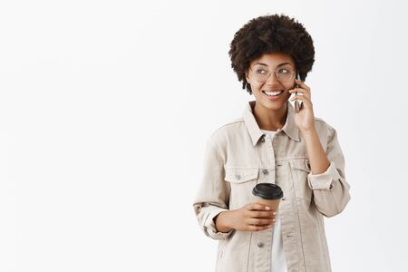 Making arrangements via smartphone. Portrait of talkative friendly and attractive dark-skinned female model in glasses and shirt holding paper cup of coffee and talking on cellphone gazing left