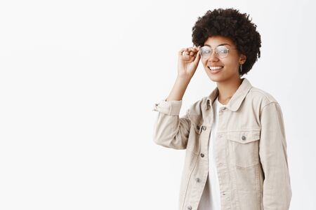 Waist-up shot of cool confident and stylish boyish woman with afro hairstyle touching rim of glasses on eyes and smiling broadly at camera
