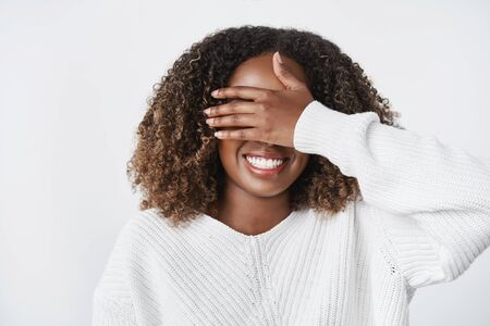 Charming happy and thrilled cute african-american girlfriend close sight with palm and anticipate gift wearing warm sweater over white wall 版權商用圖片