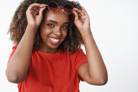 Close-up shot of happy satisfied and carefree african american woman forgetting about cold winter days sipping cocktail on beach during holidays as travel to warm country taking of sunglasses smiling