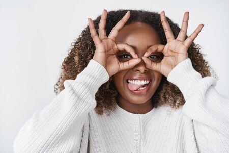Girl fooling around feeling happy and joyful showing tongue aping and making goggles using hands on eyes having fun feeling like child relaxing and enjoying life 版權商用圖片