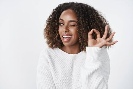 Relaxed and unbothered confident good-looking successful african american woman winking cheeky and smiling as showing okay gesture, assuring everything perfect 版權商用圖片