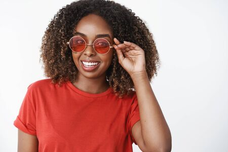 Portrait of charming carefree enthusiastic african-american female with curly haircut wearing stylish red sunglasses and gazing upbeat at camera over white wall