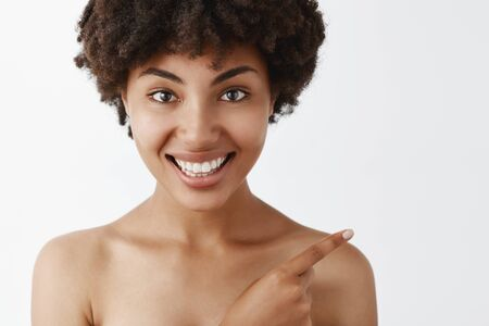 Close-up shot of attractive and beautiful dark-skinned woman with curly hairstyle pointing at upper right corner and smiling joyfully helping out to find way Stok Fotoğraf - 130176272